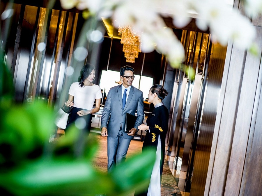 a staff is showing guests around intercontinental hanoi landmark72 5 star hotel in Hanoi