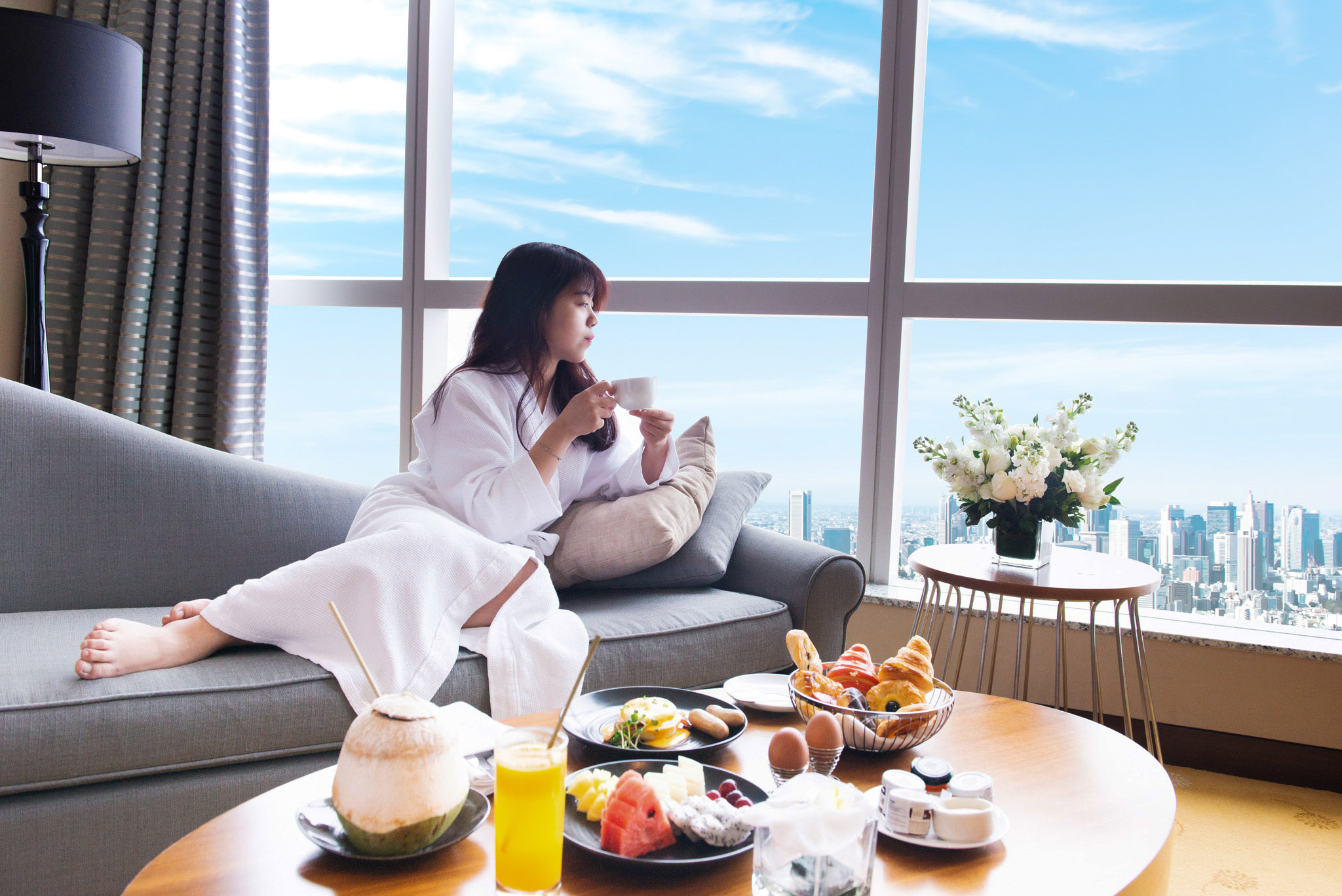 a lady enjoying breakfast in her hotel room with beautiful view of Hanoi city