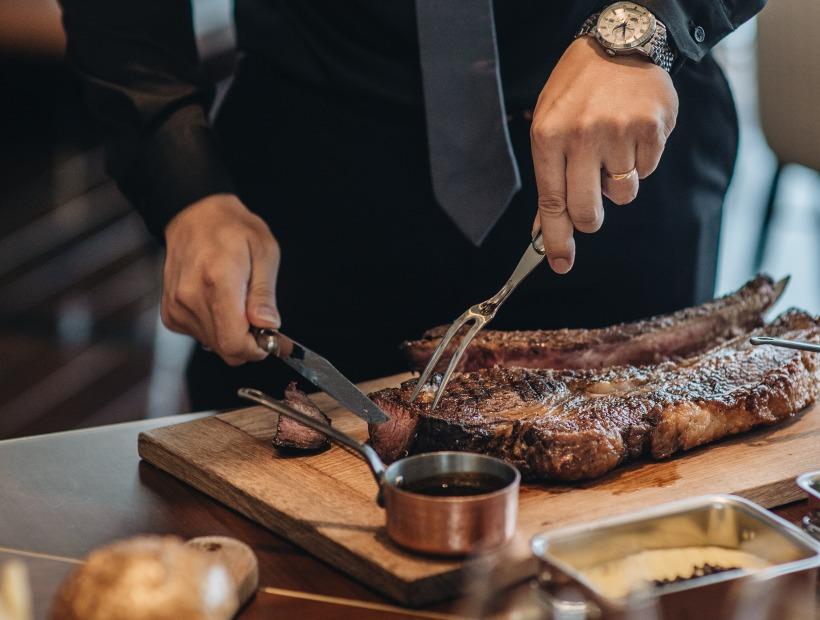 a chef cutting beef steak in a Hanoi hotel restaurant
